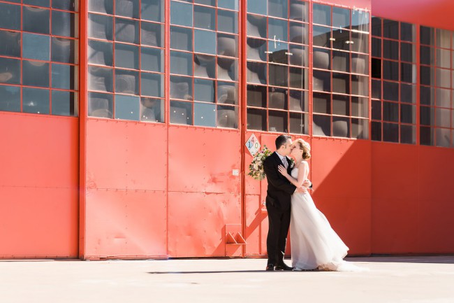 couple kiss in front of Hangar at Stanley