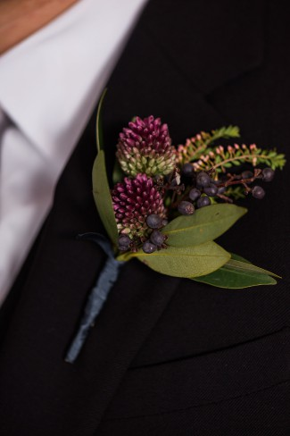 green leaf and dark purple berry boutonniere