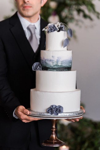 groom holds cake on stand