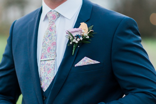 groom in blue suit with boutonniere
