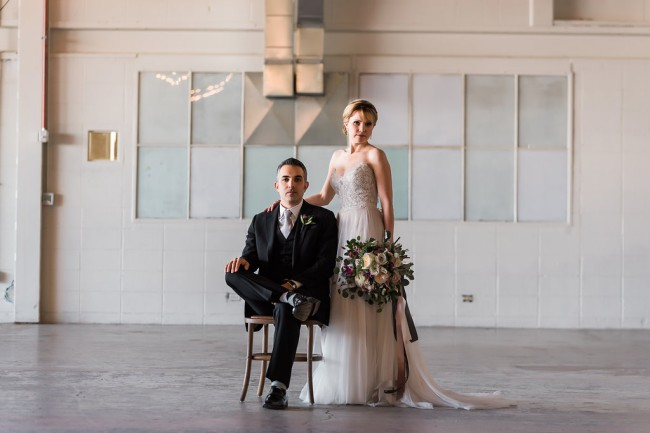 groom seated with bride standing