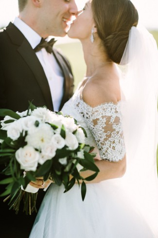 newlyweds kiss and bride holds bouquet