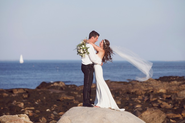 newlyweds on rocks with veil blowing