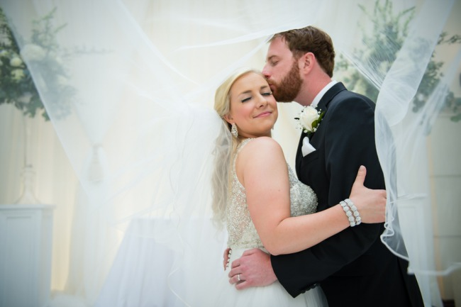 newlyweds under bridal veil