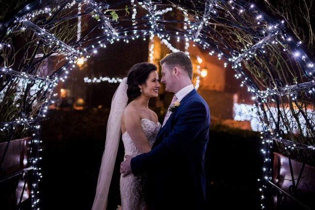 newlyweds under lights at night