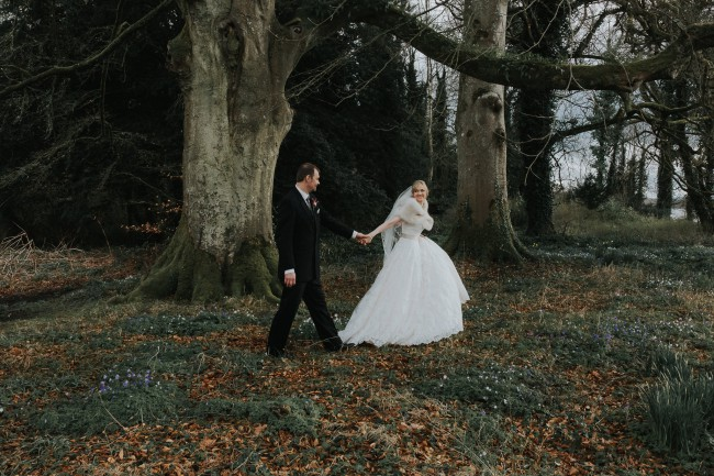 newlyweds walk in bluebell forest