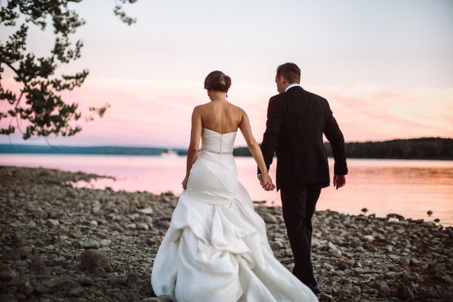newlyweds walk on beach with sunset