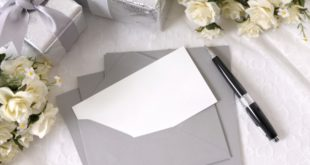 Writing paper or wedding invitation with envelope laid on bridal lace with several wedding gifts