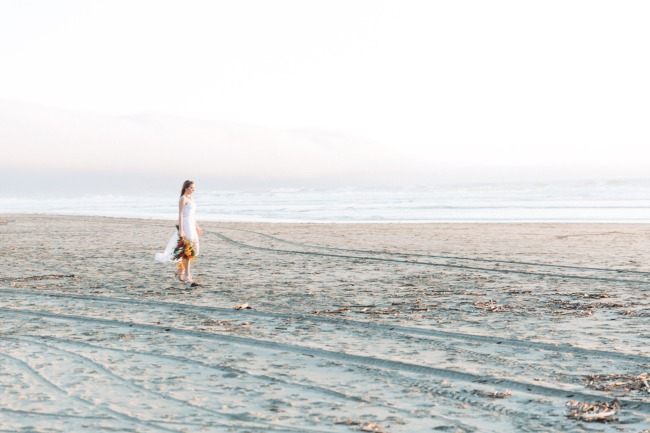 styled bride walks on beach