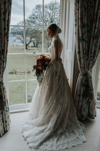 veiled bride with bouquet at window