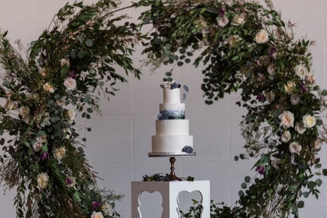 wedding cake with greenery wreath backdrop