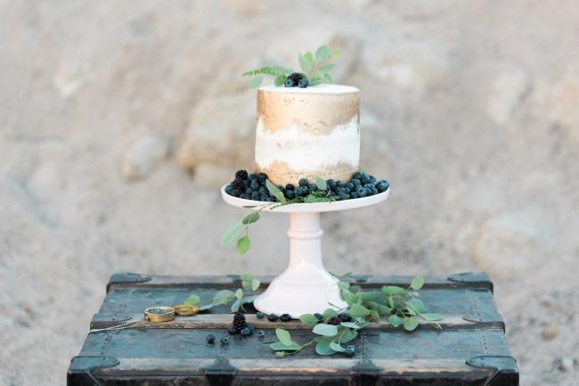 blueberry topped naked cake on white platter
