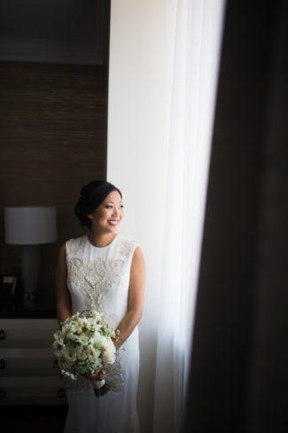 bride in window holding bouquet