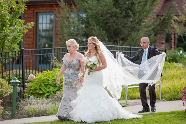 bride walking down aisle with veil held behind