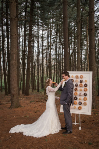 couple feed each other donuts from wall