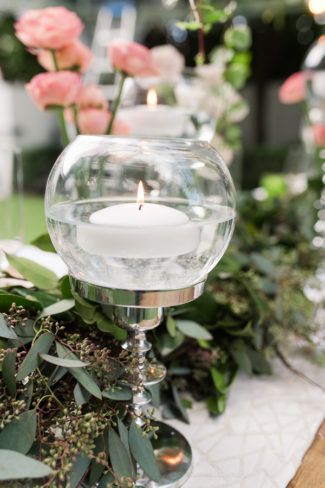 floating white votive candle in goblet