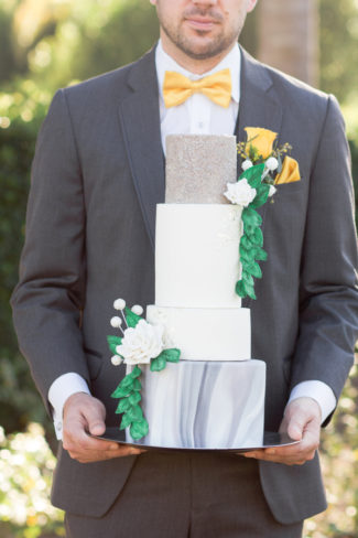 groom holding four tier industrial wedding cake