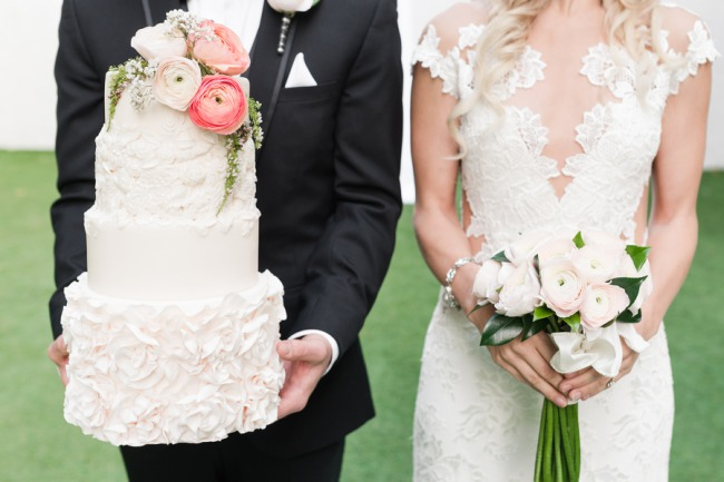groom holds cake while bride holds bouquet