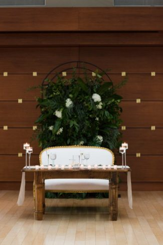 head table with greenery backdrop