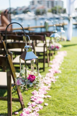 lanterns with flowers hang on hooks down aisle