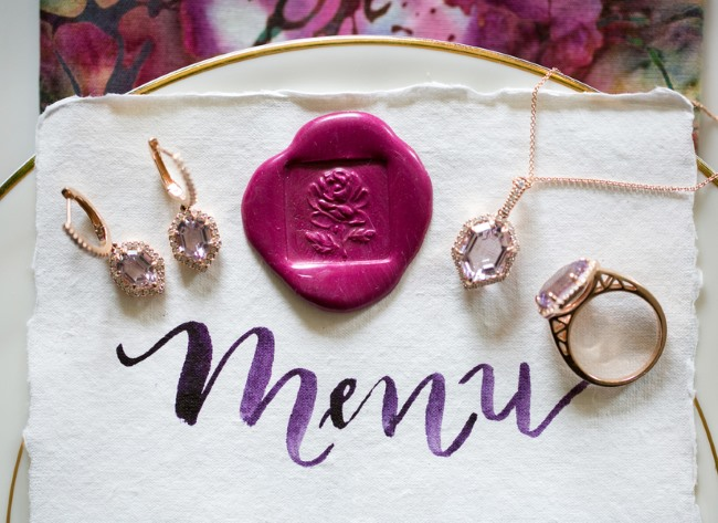 menu with fuschia wax seal and jewelry on top