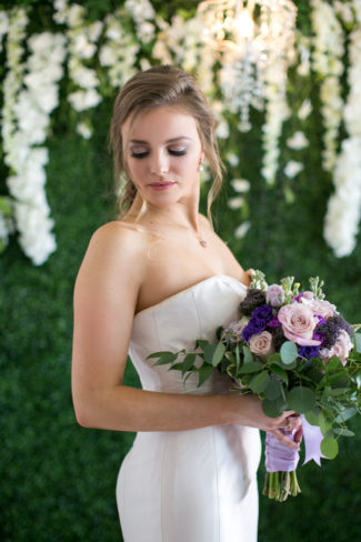 model with bouquet in front of greenery backdrop