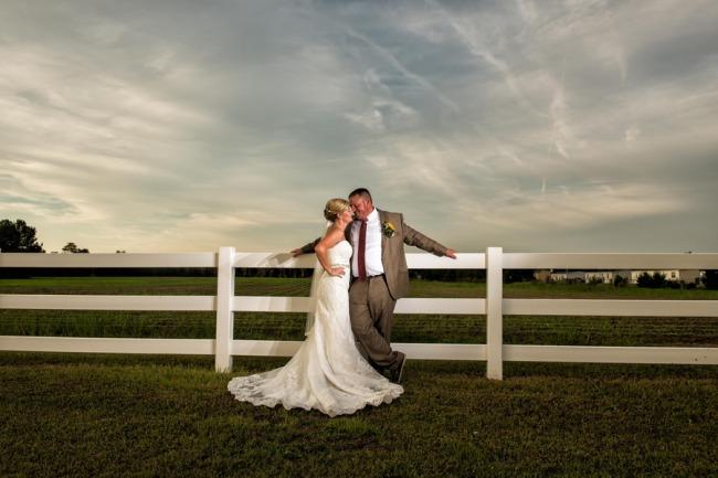 newlyweds at dusk against white fence