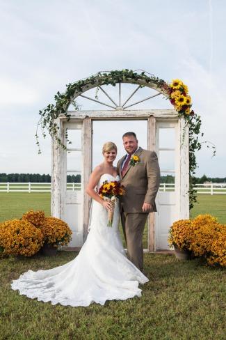newlyweds in front of doorframe alter