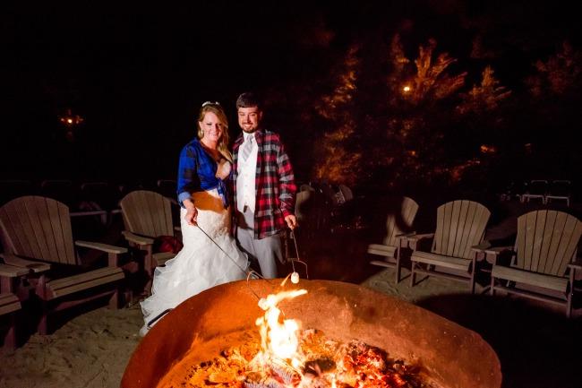 newlyweds roast marshmellows at campfire