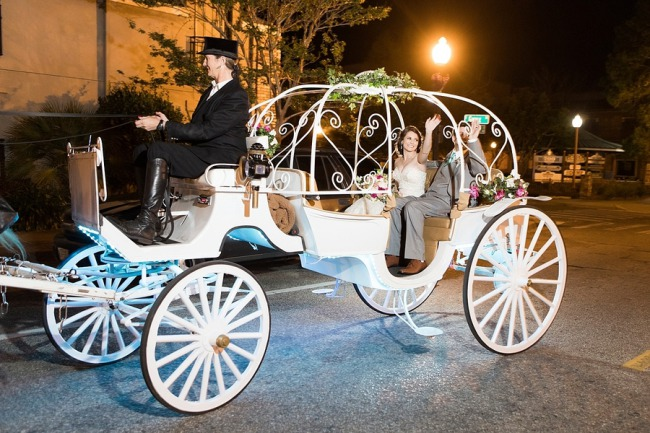 newlyweds wave from horse drawn carriage at night