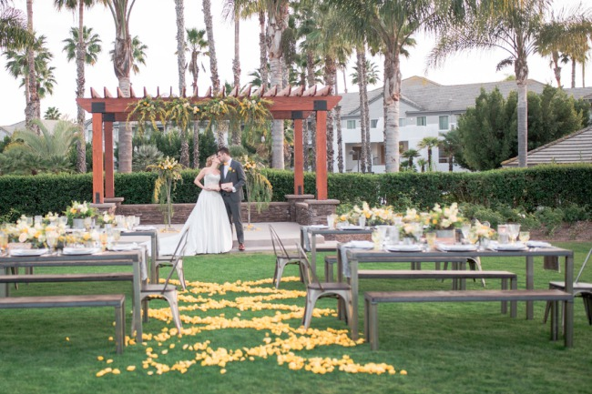 outdoor ceremony space with yellow petals and picnic tables