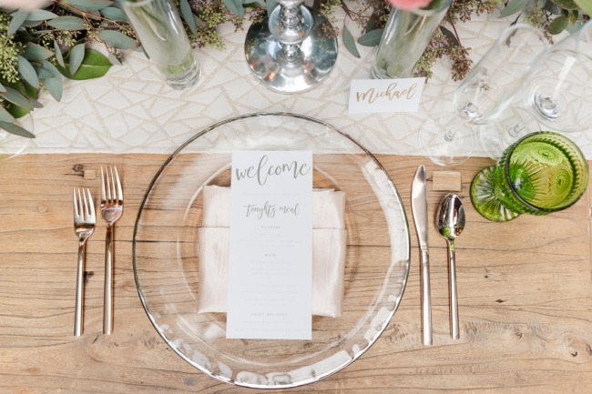 overhead table setting photo with clear plate, menu, green glass