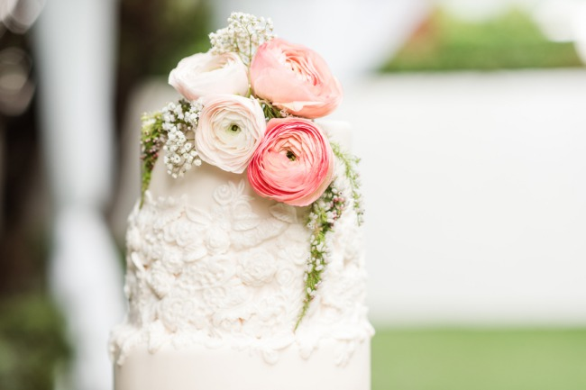 pastel pink flowers on top of wedding cake
