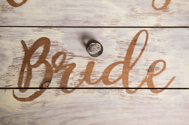 ring on wood panel that says Bride