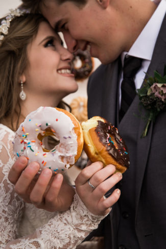 styled couple holding donuts