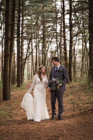 styled couple walk in Missouri woods