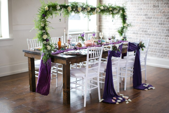 styled table with green arbor and purple fabric tied to chairs