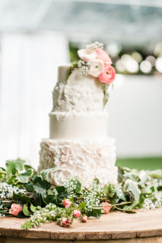 wedding cake surrounded by greenery