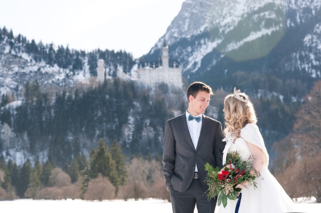 bride and groom stand with Neuschwanstein Castle behind
