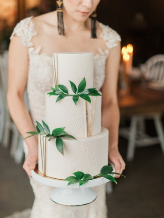 bride holding cake in Cinder Winery cellar