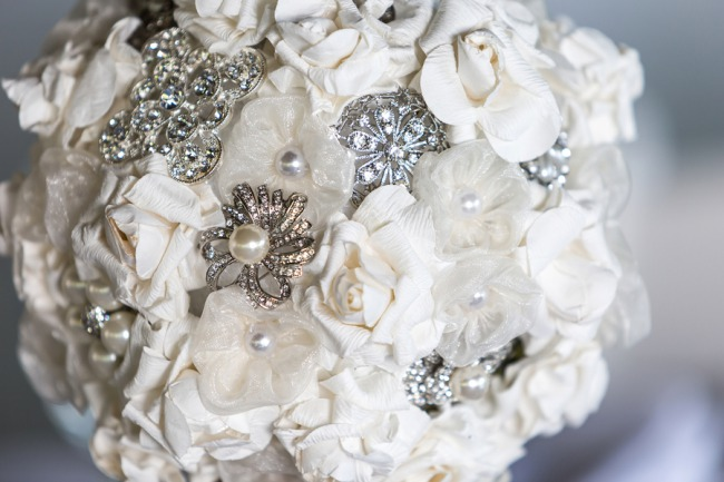 closeup of handmade brooch and white flower bouqet