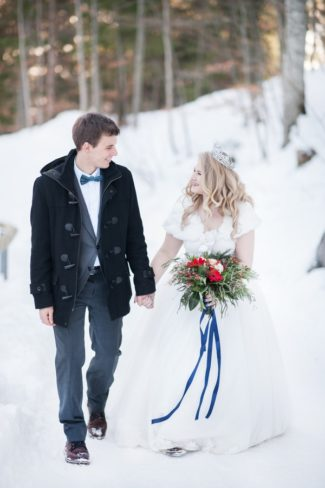 couple walk through snowy forest