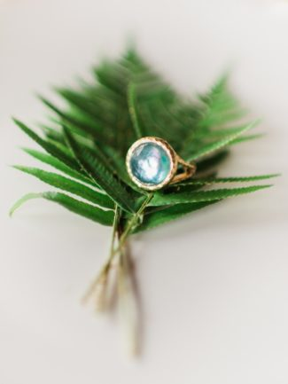 gemstone ring on greenery foliage
