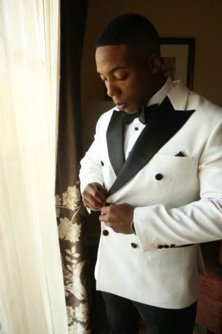 groom in white tuxedo jacket