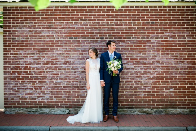 newlyweds against red brick wall