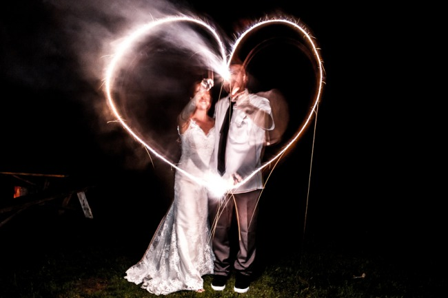 newlyweds make heart from sparklers