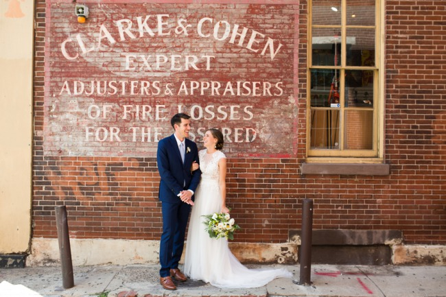 newlyweds photo against brick wall