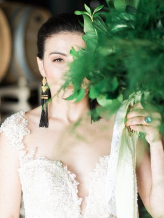 styled greenery bride hides behind bouquet