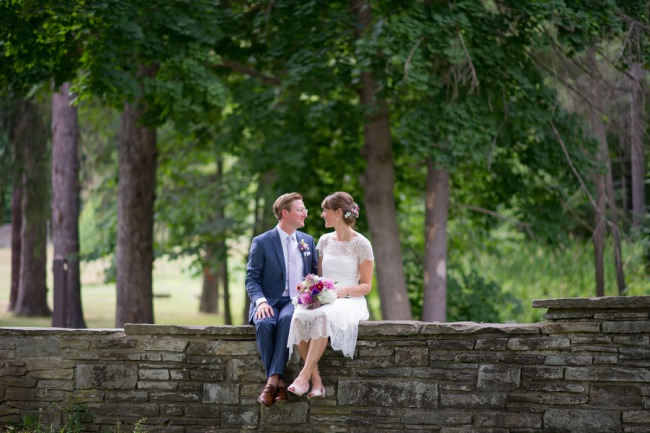 couple sit together on stone wall