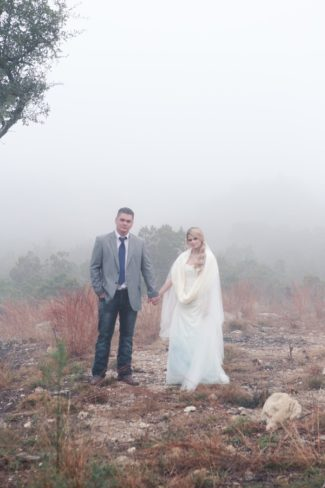 couple stand on rocky ground with fog